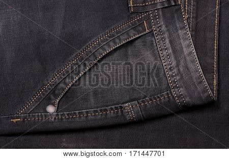 front pocket of dark jeans close up.