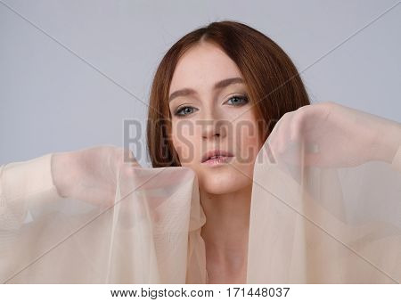 Scarf creme, emotional movement, hands relaxed. Fashion, romance, theater. Warm colors, isolated on gray.