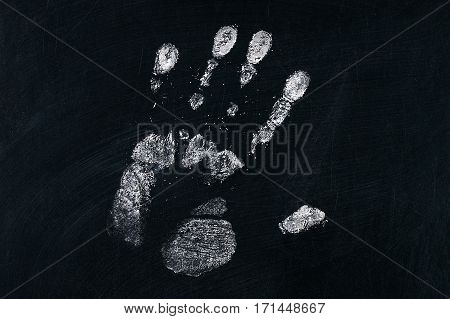 Handprint on chalkboard texture with chalk .