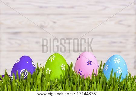 Pastel Colored Easter Eggs In Green Grass Over Rustic Wooden Background.