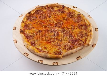 Delicious hot pizza with pepperoni - thin pastry crust at wooden round desk isolated at white background.