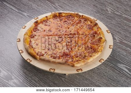 Delicious hot pizza with pepperoni - thin pastry crust at wooden round desk on wooden table.