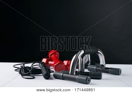 Accessories for fitness. Dumbbells skipping rope push up bars against dark background. Copy space