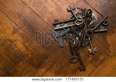 Top view of rusty old keys on brown wooden background. Copy space