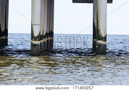 Concrete piers concrete columns protrude from the water at the pier of Scheveningen in the Netherlands.