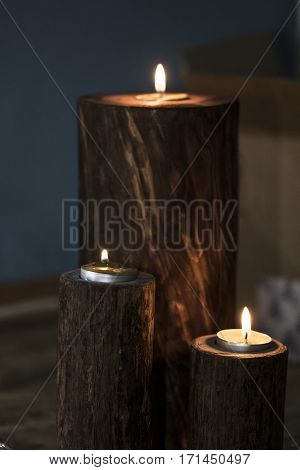 A White Candle With Dark Background - In A Wooden Candlestick