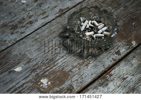 Cigarette butts in an ashtray on old wooden background.Copy space.