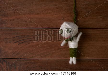 Hanged voodoo doll on wooden background.Copy space.