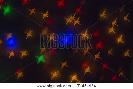 Out of focus and blurred colored star shape lights on black background.