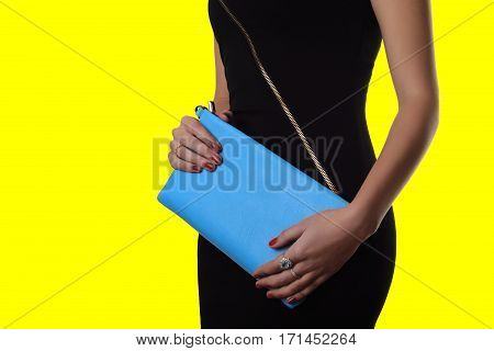 Indoor Trendy Girl Near Yellow Background .black Dress And Blue Clutch
