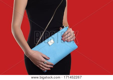 The Fashionable Young Woman In Black Dress Holding Blue Clutch. Red Background