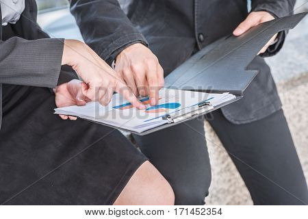 Close up hand of businessman and woman pointing at business document while they discussing outdoor.