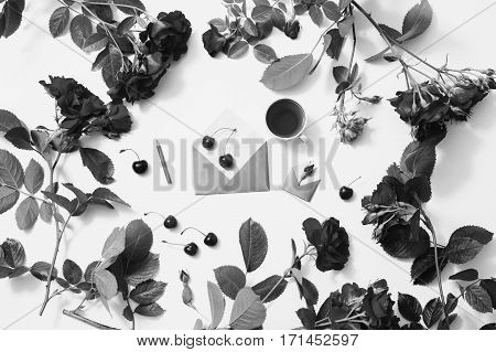 Black and white art photography monochrome rose tea ripe cherries small envelopes with green leaves rose lay on white background. Tea drinking during work. Healing drink. Berry compote. Flat lay