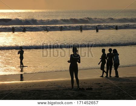 -  the popular island in Indonesia. Silhouette of people at sunset over ocean at Kuta