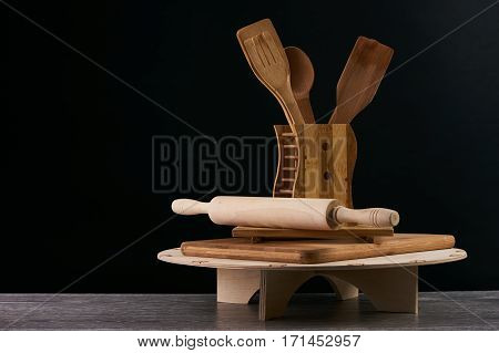 Set of the wooden kitchen utensils on black background. spoon kitchen spatula rolling pin fork copy space.