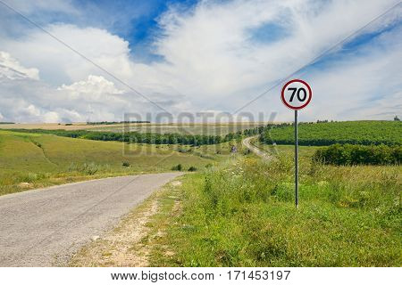Road sign limiting speed on a country road. Bright sunny day.