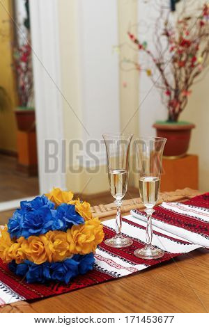 two glasses filled with champagne on table with blue and yellow flowers and ukrainian embroidered towel. official wedding registration ceremony in hall
