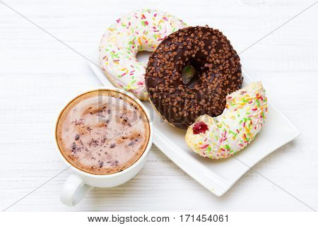 Cup of coffee and tasty donuts with icing and chocolate on white wooden background copy space