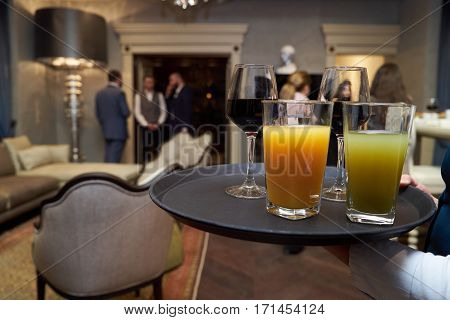 Waiter with dish of wine and juice glasses at the opening ceremony.
