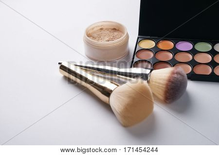 Make up professional cosmetics palette with eyeshadow and brush on it isolated on white. Professional make-up tools closed-up.Copy space.