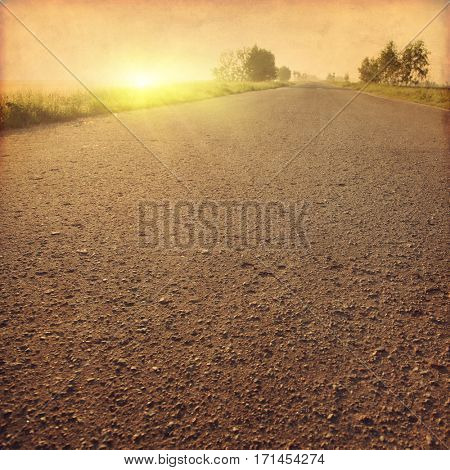 Country asphalt road at sunset in grunge and retro style.