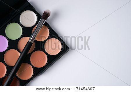 Make up professional cosmetics palette with eyeshadow and brush on it isolated on white. Professional make-up tools closed-up.Top view with copy space.
