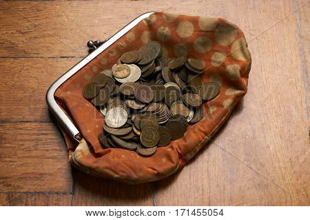 Old retrovintage woman wallet with old collection coins on wooden background.