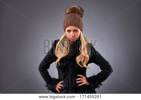 A beautiful young woman in an elegant black sweater and a brown hat and feeling upset