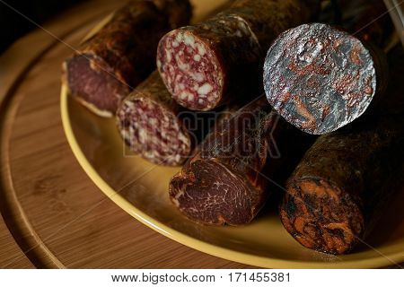 Closeup photo of a different delicacy salami smoked sausage on wooden board