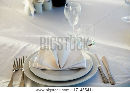 Linen Napkin On A Plate On The Table Covered With A White Tablecloth.
