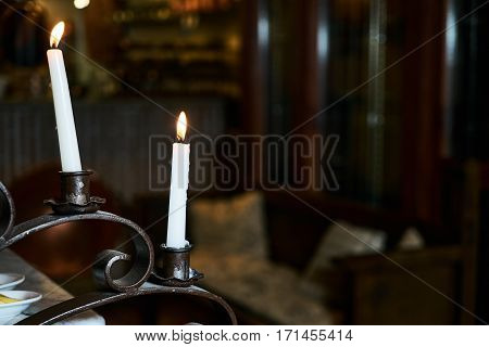 Standing brass candlestick with burning white candles in shallow focus home setting.Romantic concept.