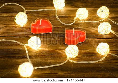 Two candles in shape of heart among the glowing lanterns made of rattan on a wooden background. Side view closeup