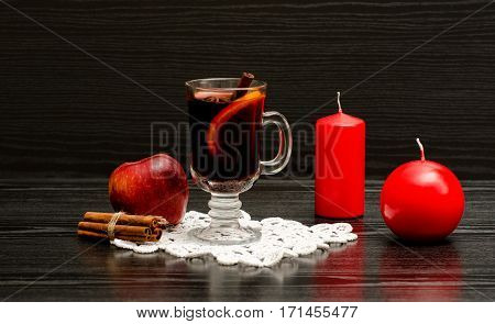 Mulled wine with spices on a lace napkin. Red candles cinnamon sticks and apple. Black wood background
