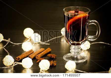 Mug of mulled wine with spices cinnamon sticks star anise. Illumination of rattan lanterns on a black wooden table