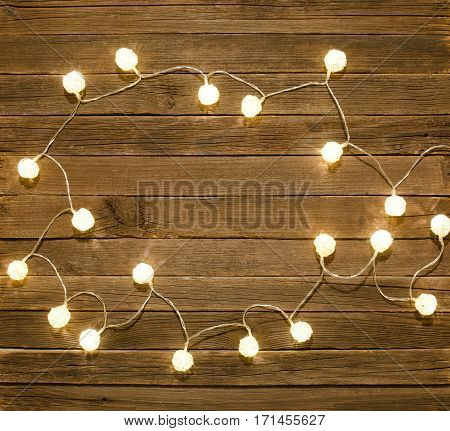 Vintage wooden background framed by garlands of rattan lanterns. Top view space for text