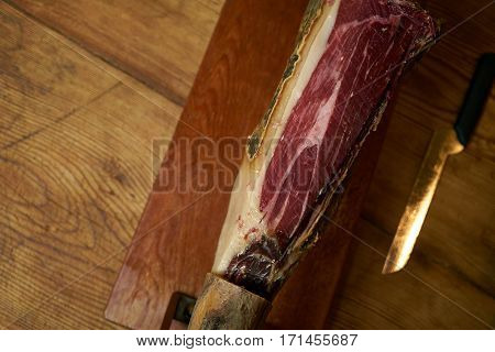 Smoked leg of lamb on wooden cutting board with knife.Woooden background with copy space.