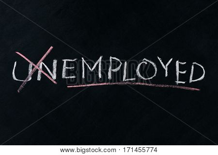 Turning the word Unemployed into Employed on chalkboard business concept.