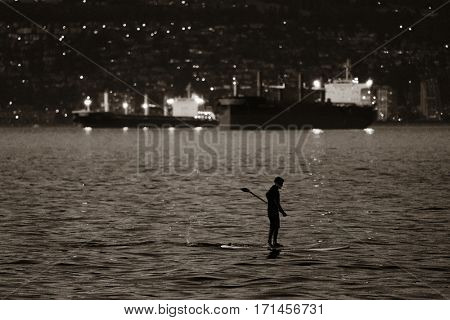 A man row boat in sea in Vancouver at dusk