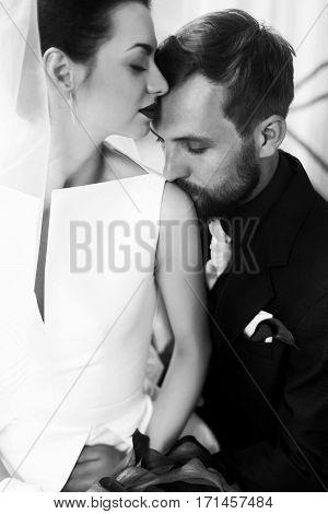 Elegant Stylish Groom Gently Kissing In Shoulder Gorgeous Bride In Light. Unusual Wedding Couple In