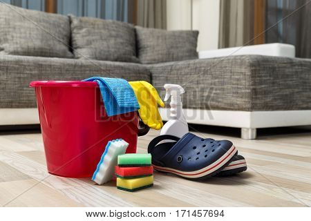 Cleaning service. Bucket with sponges, chemicals bottle and boating shoes. Rubber gloves and towel. Household equipment.