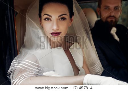 Luxury Elegant Wedding Couple Posing In Stylish Black Car. Gorgeous Bride Portrait And Handsome Groo
