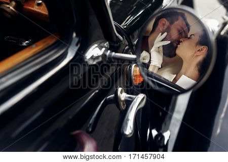 Luxury Elegant Wedding Couple Kissing And Embracing In Stylish Black Car. Unusual View In Mirror. Go