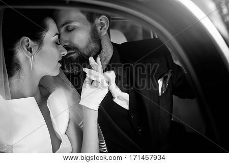 Luxury Elegant Wedding Couple Kissing And Embracing In Stylish Black Car. Gorgeous Bride And Handsom