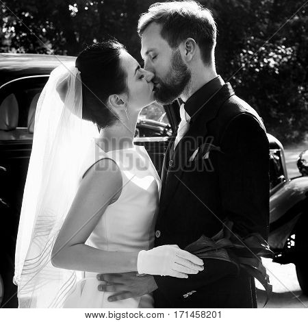elegant gorgeous bride and handsome stylish groom kissing on background of black car. unusual luxury wedding couple in retro style. romantic moment.black white photo
