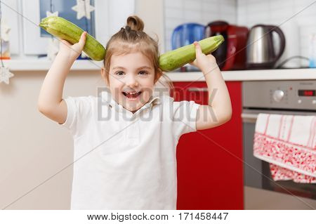 Little kid with two zucchini stands in kitchen