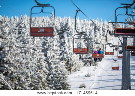 Ski lift with skiers being carried up the hill on a lovely, sunny winter day