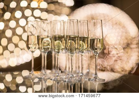 Champagne flutes on shiny, glassy background with lovely blurred lights in the background