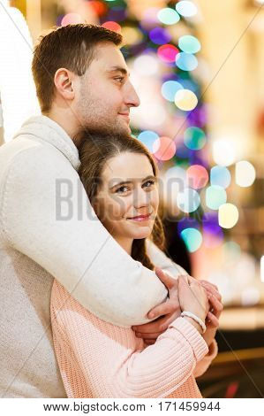 Beautiful boy and girl hugging in room on background of lights