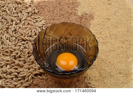 Organic Wholemeal Pasta, Flour And Wheat Germ With A Bowl With An Egg In It On A Rustic Wooden Table