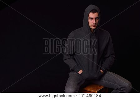 Horizontal Head Shot Of A Confident Young Man Wearing A Black Hoodie Posing On A Black Background. S